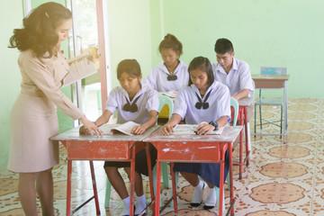Beautiful Thai Teacher in uniform standing at classroom teaching student