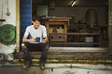 A man in a teeshirt having a tea break, sitting on the steps of a workshop checking his phone.