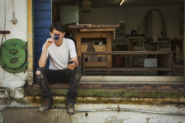 A man in a teeshirt sitting on a step drinking from a cup, holding his smart phone.