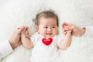 両親と手をつなぐ赤ちゃん