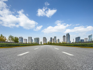 city road through modern buildings against blue sky