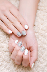 Female hands with white and gray nail design