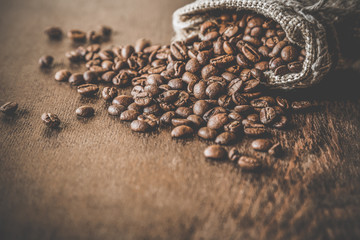 Wall Murals Coffee beans Brown beans with burlap bag on the wooden table. Harvest of coffee in different countries. Choice of the best sort and quality coffee. Rustic atmosphere. Advertising concept.