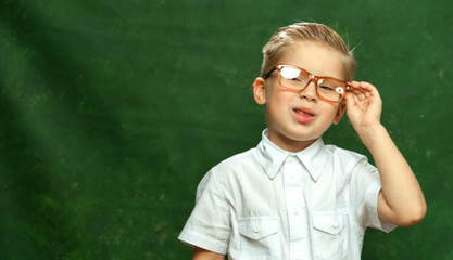 Blurred portrait Stylish little fair-haired boy in white shirt smiles and holds with one-hand glasses on dark background
