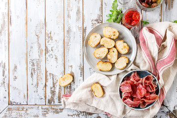 Ingredients for making tapas or bruschetta. Crusty bread, ham prosciutto, sun dried tomatoes, olive oil, olives, pepper, greens on plates over white plank wooden table. Top view with space