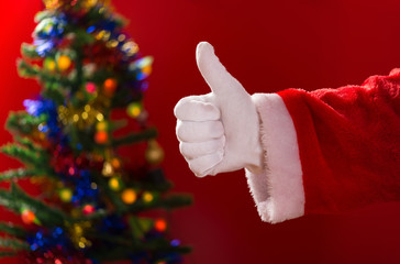 Santa Claus doing a thumbs up gesture with decorated Christmas tree on background