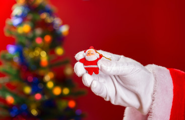Santa Claus holding a doll on hand with decorated Christmas tree on background