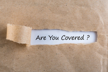 ARE YOU COVERED? Question message appearing behind ripped brown paper. Are you insured for your car, travel, home, health or other liability