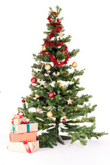 Decorated Christmas tree with heap of gift boxes near it on white background