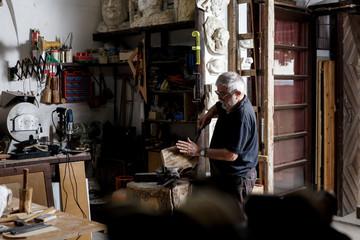 Senior man working on his wooden sculpture in his workshop.