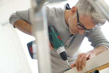 Man assembling DIY furniture using electric drill