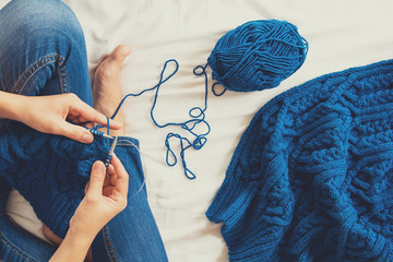 Woman knitting blue sweater. Overhead shot