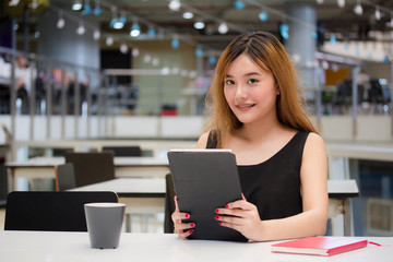 Beautiful young adult thai chinese bronze hair show her tablet.