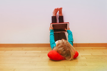 little girl looking at touch pad, home learning