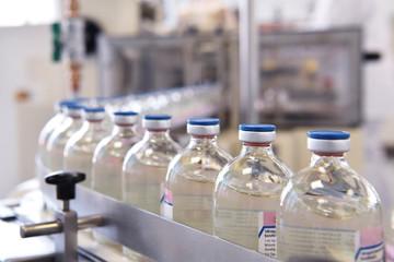 Produktion von Medikamenten - fliessband mit Arzneimittel in Glasflaschen auf einem Fliessband in der Pharmaindustrie