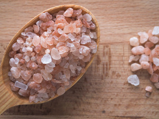 Large pink salt and wooden spoon on wooden table.