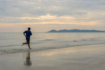 Men running on the beach and sea water