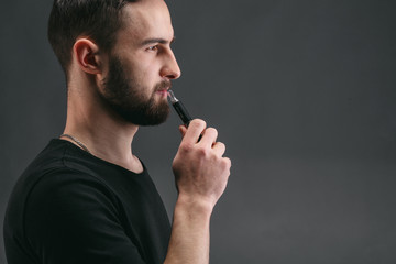 Young man vaping e-cigarette with smoke on black