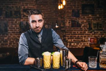 Barman serving drinks, working at bar
