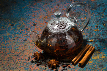 tea masala in a glass teapot on a dark background, top view