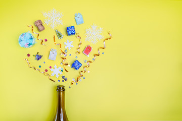Part of champagne party bottle with confetti of gifts, sequins, ribbons, snowflakes on bright yellow background. Flat lay. Celebrate new year concept. Selective focus, space for text
