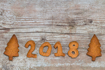 Happy New Year 2018 concept - number 2018 with gingerbread on wooden background