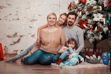 New Year's photo of family sitting at decorated Christmas tree