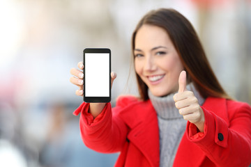 Woman showing smart phone screen in winter