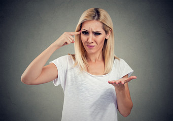 Closeup portrait of angry mad woman gesturing with her finger asking are you crazy? Isolated on gray background.