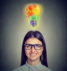 Portrait of a woman with glasses and creative idea looking up at colorful light bulb on gray background. Inspiration concept