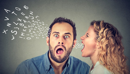 Angry woman screaming something in the ear of a shocked, scared guy isolated on gray wall background.