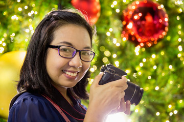 Woman with camera and Christmas decorative light bokeh background