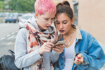 two young women outdoors using smart phone - online, youth culture, social network concept