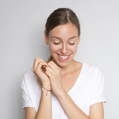 Beautiful brunette caucasian woman in white blouse with bright emotions standing on a neutral grey background. Her hands make a gesture. She smiling happily