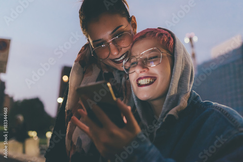 two young women outdoors in the night using smart phone face
