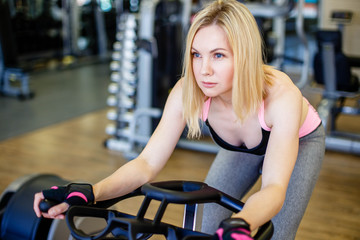 Muscular young woman working out on the exercise bike at the gym, intense cardio workout