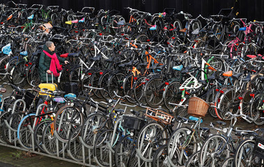 A woman pulls her luggage while walking among hundreds of bicycles outside central train station in Amsterdam