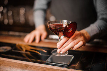 Barman holding a glass of red decorated alcoholic drink