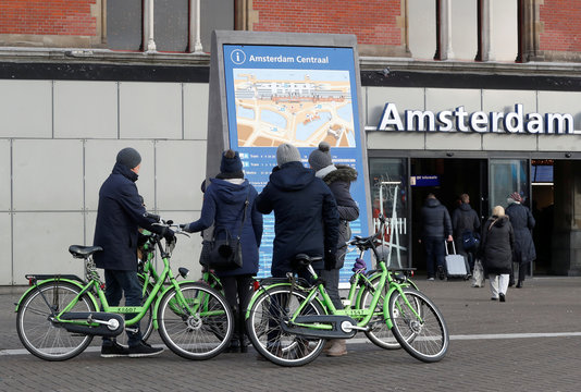 People stand next to rental bicycles while looking at a map outside central train station in Amsterdam