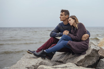 Happy thoughtful couple sitting on a rock beach near sea hugging each other in cold foggy cloudy autumn weather. Copy space