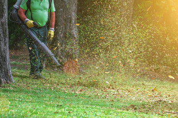 Man working with leaf blower in the park.