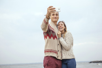 Happy thoughtful couple standing on a rock beach near sea hugging each other in cold foggy cloudy autumn weather. Man photograph them on a phone. Copy space