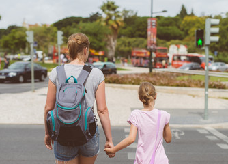 Mother and daughter crossing the road. Back view.