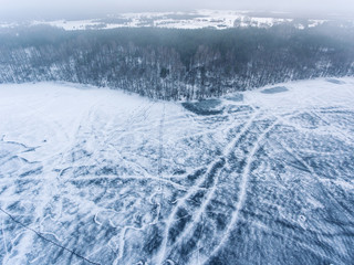 Flight over frozen lake breaking ice in rural village, Lithuania. Aerial photography during winter season.