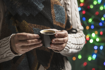 Coffee in woman hands on a Christmas background.
