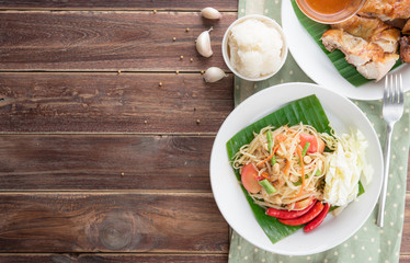 Green papaya salad,Som tum Thai and grilled chicken on wood table,top view