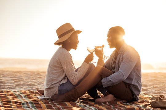 Young African couple drinking wine at the beach at dusk