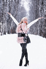 Snowy day blonde girl on a walk in a winter park