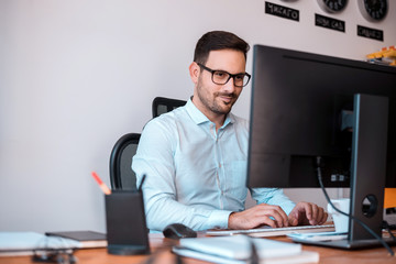 Delighted programmer with glasses using a computer.