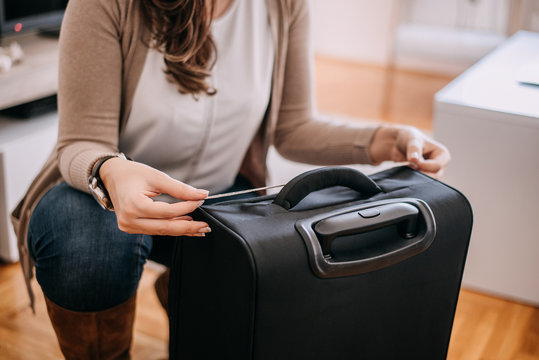 Woman inspecting hand luggage measurement using measuring tape.